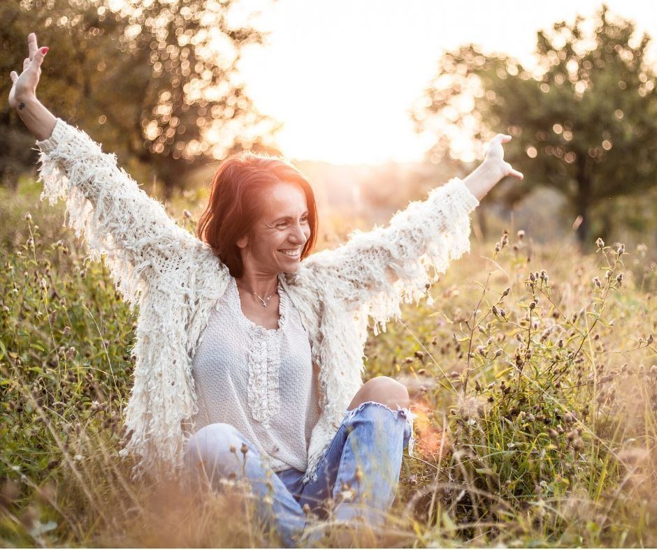 White woman sitting in a field with her hands up in the air